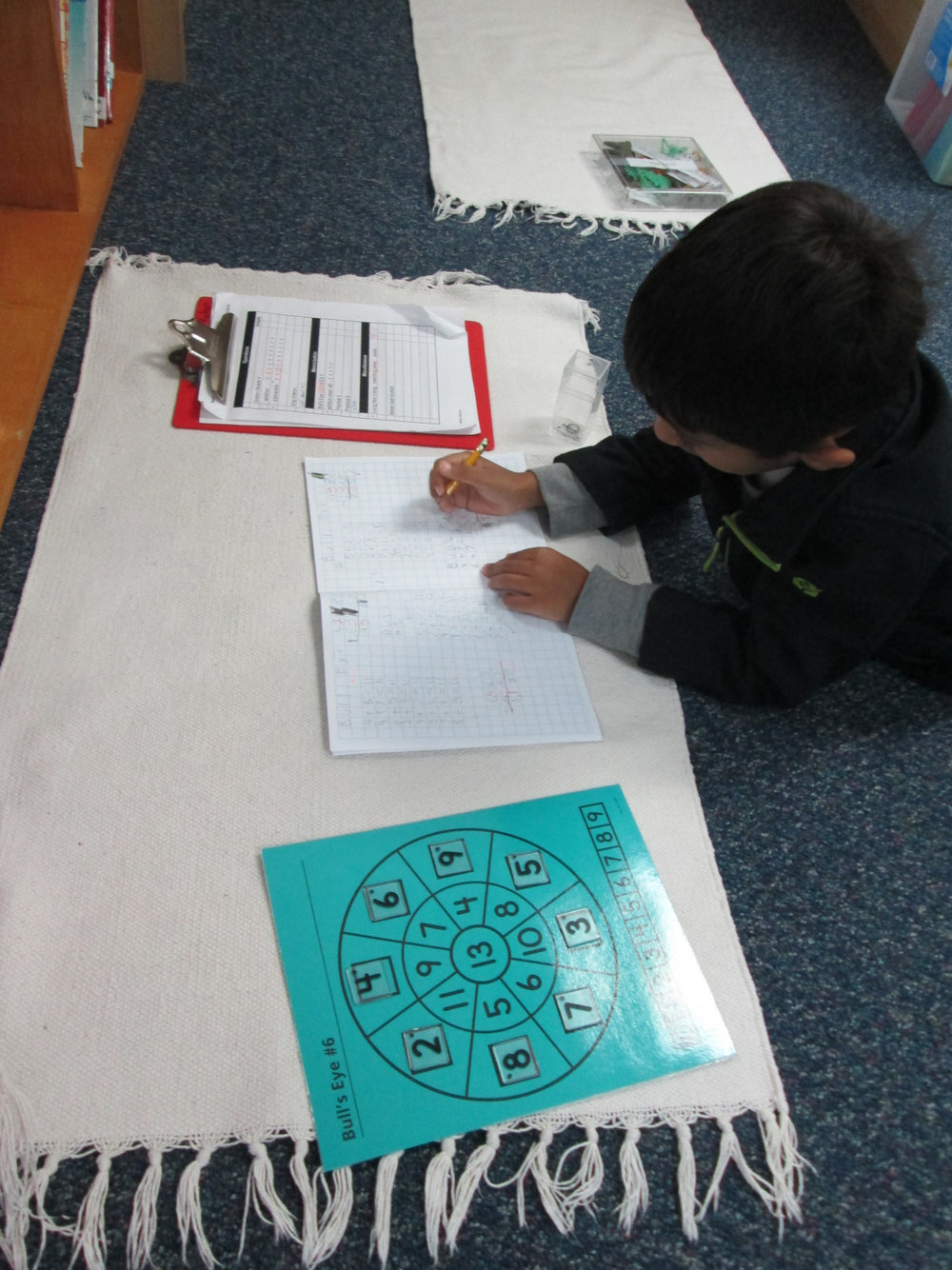 A first grade Lower Elementary East student worked diligently to learn math facts. The Math puzzles in the classroom help the students have fun while mastering these important math facts.