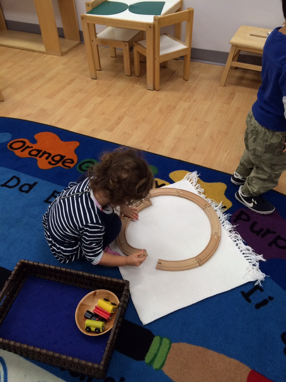 Even Toddler 1 students work on basic geometry.   The challenge:  Will curved pieces make a circle?