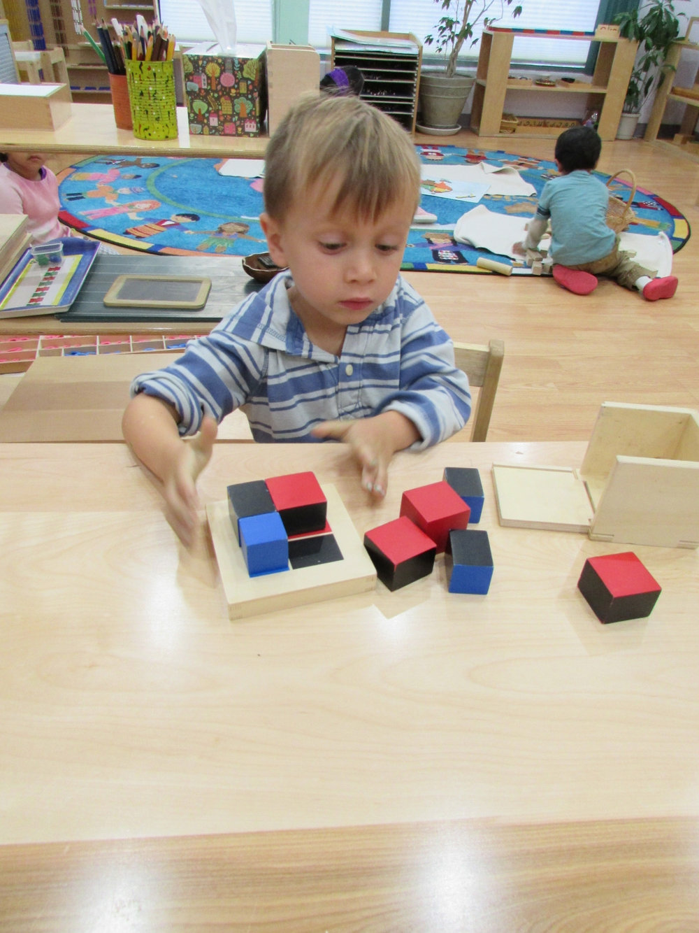 A Primary 2 student worked with the Binomial Cube, a material that promotes problem solving, helps a student to identify dimensions and prepares the student to learn algebraic concepts in the future.