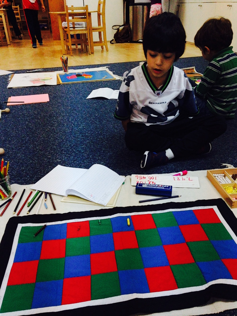 Second grade Lower Elementary West students received an introductory lesson in the use of the Checkerboard material. This lesson helps to strengthen a student's understanding of place value as well as reading and writing numbers. Later on, the same Checkerboard material is used for large scale multiplication problems.