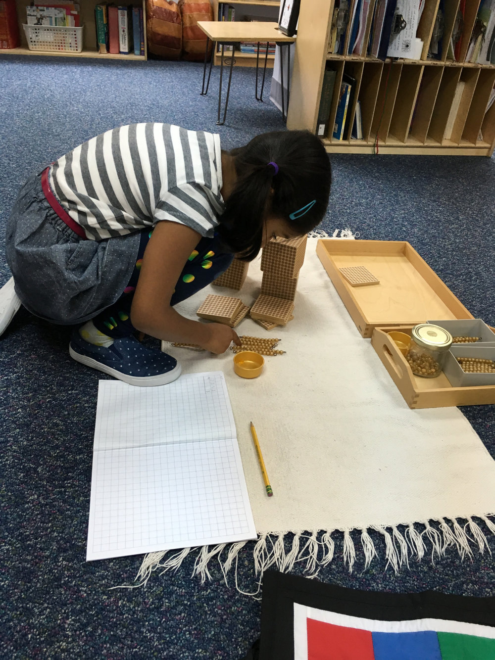 A first grade Lower Elementary West student used the Golden Beads to work on multiplication problem solving.  The Golden Beads material is a staple in every Montessori classroom and is used by students at all academic levels throughout the Primary Math curriculum, from reading numbers to more complex operations.