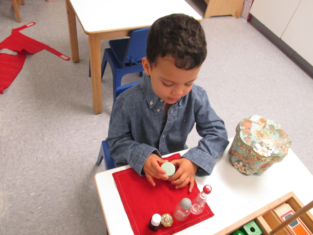 A Primary 1 student opened and closed different kinds of lids on containers, which exercised his fine motor skills and helped to strengthen his hands.