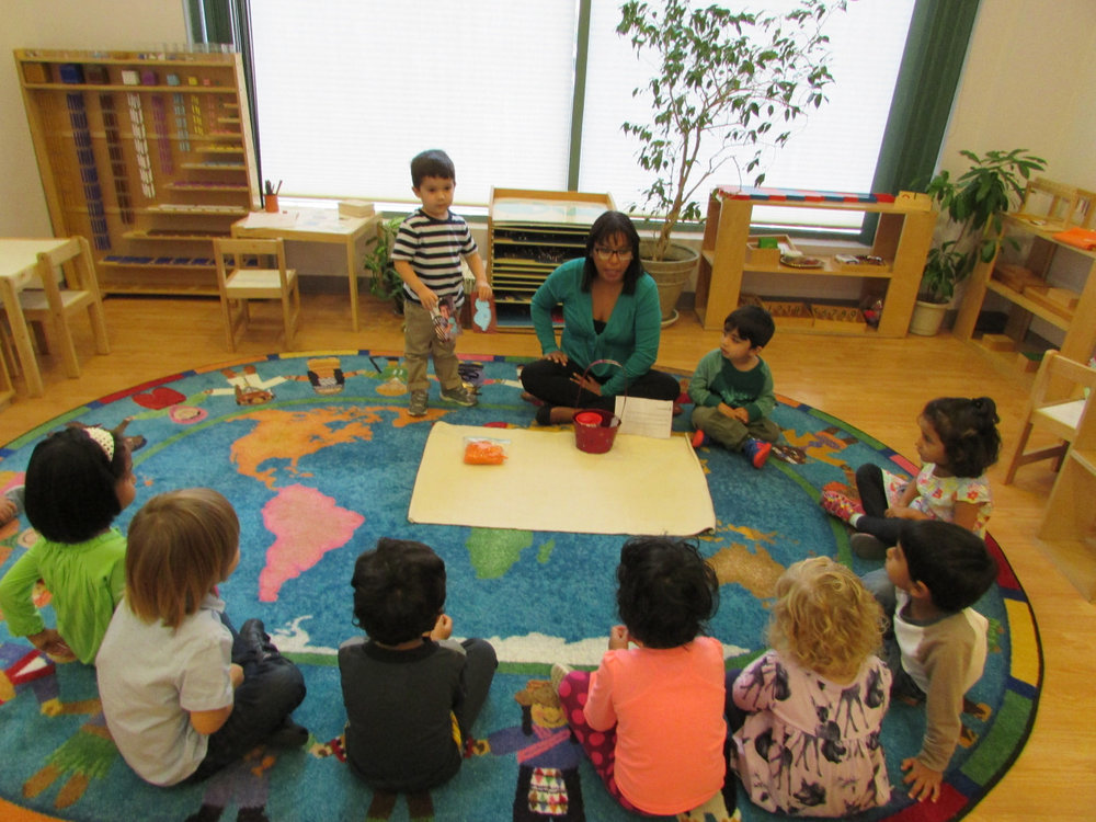 The first year Primary 2 students began their rotation to bring home the sound basket with an assigned letter.  The students collect objects that begin with that initial sound and bring them to school to share with their classmates.  In circle time, one of the students showed his classmates the objects he brought from home.