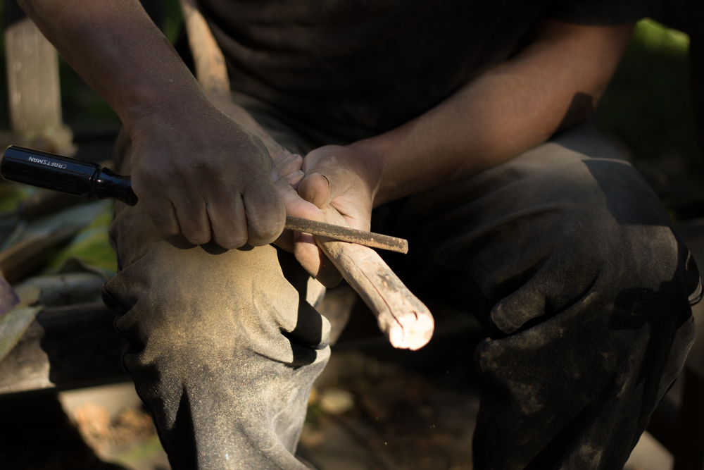 Sculpture artist Anthony Bayne uses a small rasp to shape one of his wooden canes.