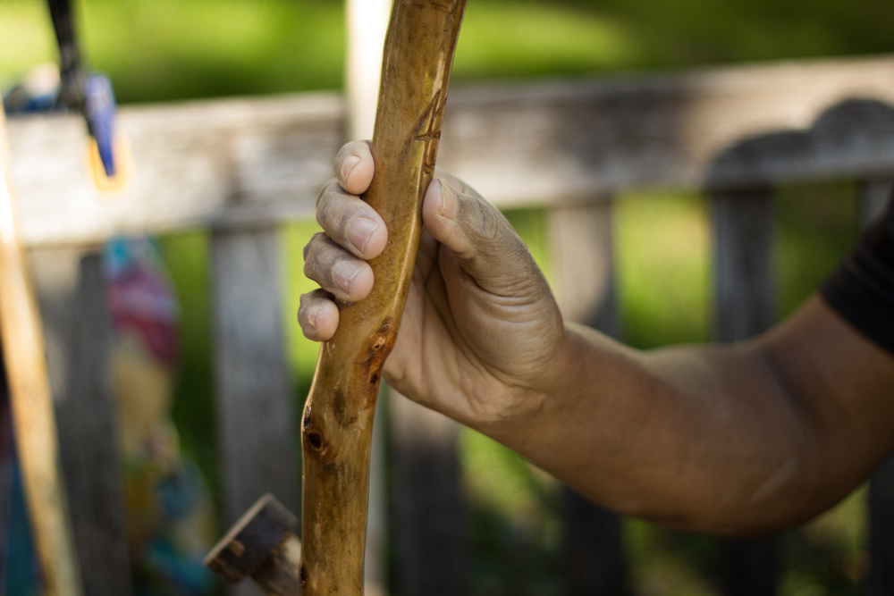 Sculpture artist Anthony Bayne holds up one of his finished, hand-carved wooden canes. In addition to carving them, he also paints some of them and seals them with several coats of polyurethane.
