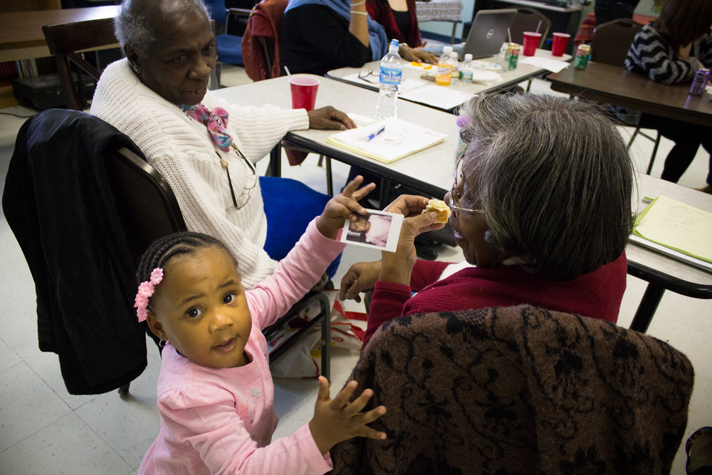 Malayja Tooles, 2, shows a photo of herself to Mary Bell, 83, during The Redline Project workshop at The Dixon House in Point Breeze January 16, 2016.