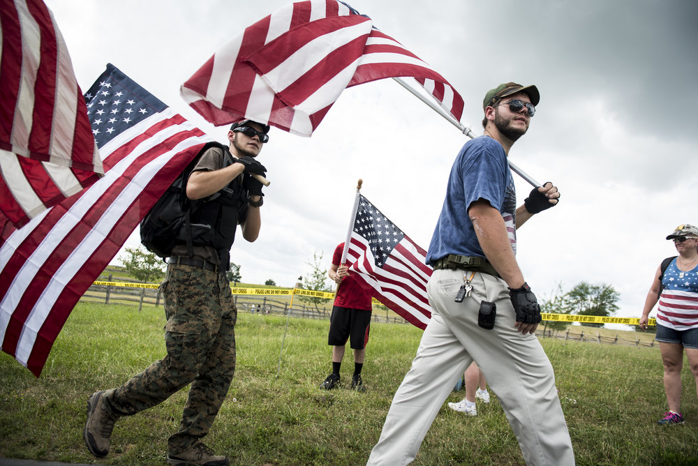 People carry American flags near a demonstration area at Gettysburg National Military Park.