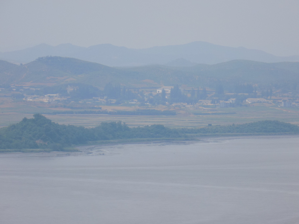 "Looking across the river at North Korea - the town is a ""fake"" town built by North Korea. No one lives there, but it was built as a display to show South Korea that the North is capable of doing anything the South does."