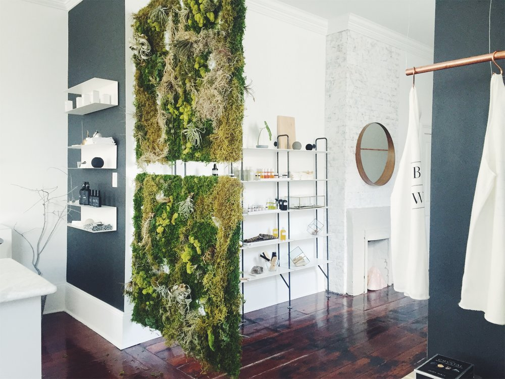 Light, open, airy, lots of white, weathered wood, insanely gorgeous crystals, fresh scents of palo santo, and a hanging succulent wall (need I say more?).