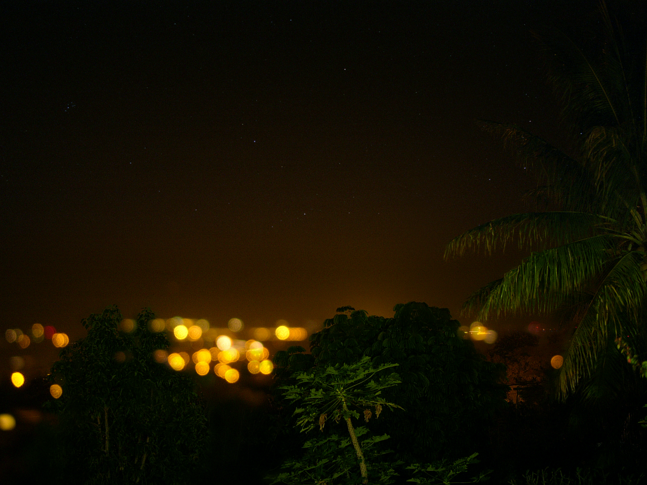 Kona, Hawaii. Looking west out over the Pacific Ocean with the warm town lights illuminating a hazy 8pm sky.