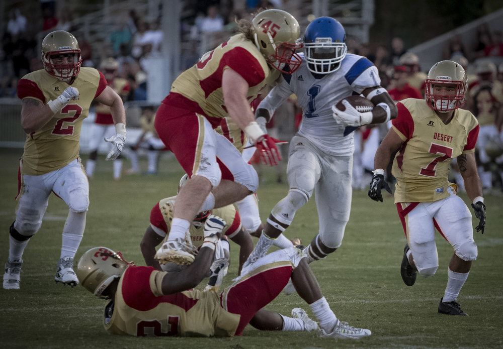 The Santa Monica College Corsairs Freshman runningback #1 Kwame Duggins (In White,Center) splits defenders linebacker #45 Chance spates (Gold,Center), and cornerback #32 T. D. Armstrong (Gold,Center) from the College of The Desert Roadrunners to score a late 2nd quarter touchdown. The Corsairs would win 68-25. Desert Springs, Calif., 9/5/2015 (Photo By: Daniel Bowyer/Corsair Staff)