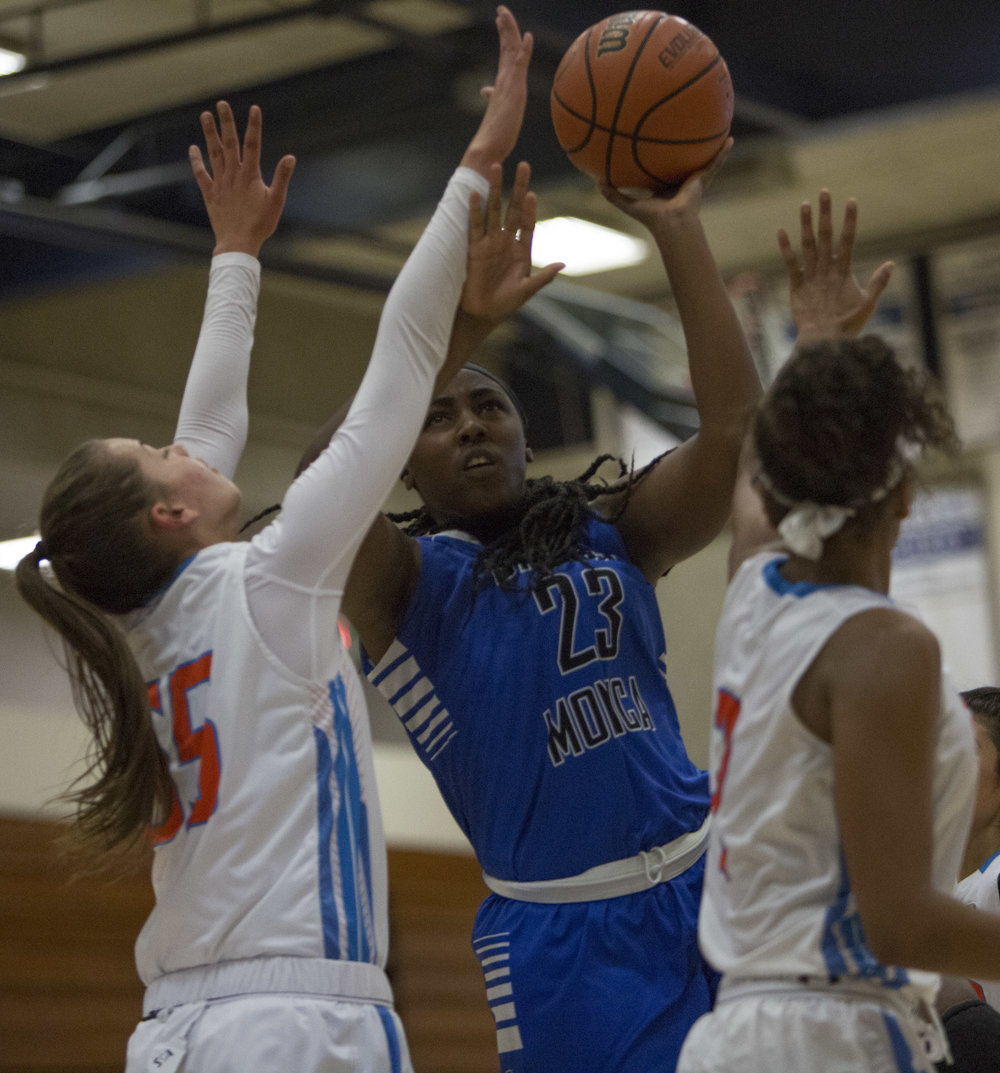 December 4th 2016. The Santa Monica College Corsair Womens Basketball team freshman center (23) Jada Gambrah (blue,center) fights her way in for a layup in-between The Citrus College Owls freshman forward (55) Celeste Fekay (white,left), and sophomore forward (2) Marisa Brown (white,right) in the 33rd annual Lady Charger Classic basketball tournament hosted by Cypress College in Cypress, Calif.. The Corsairs would win 74-69 earning them third place in the tournament. Photo By: Daniel Bowyer/Corsair Staff