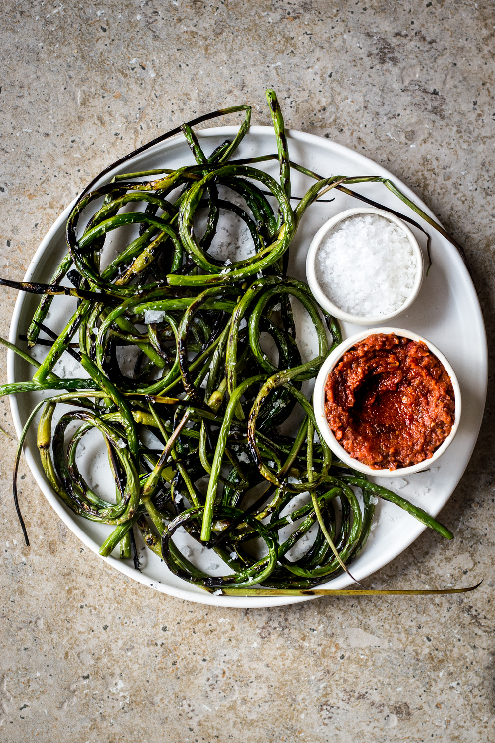 Grilled Garlic Scapes with Sun Dried Tomato Pesto and Sea Salt