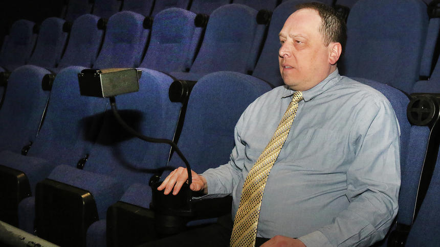 Cory Keim, general manager of Keim Theatres, shows the new wireless closed captioning devices for the hearing impaired.