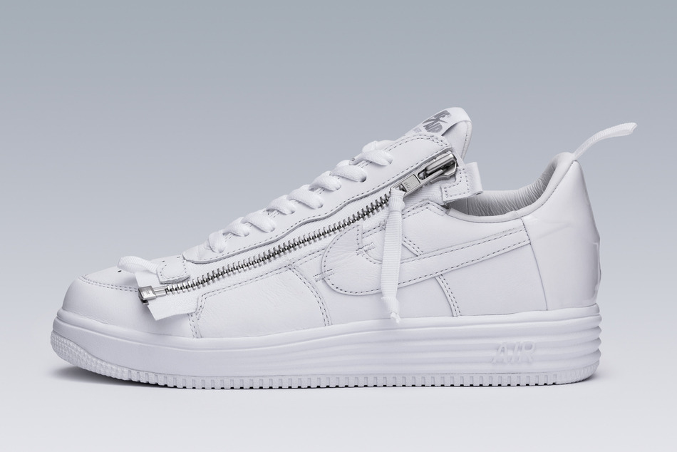 """Errolson Hugh's Acronym imprint thrives on innovation and the creation of functional apparel. He approaches everything with an innovative mindset, looking for ways to improve function and, in turn, evolve everyday life. Introduced in 2015, the ACRONYM x Lunar Force 1 design made the iconic AF-1 more functional and wearable than ever before. The 2015 shoe now returns in classic fashion, refinished in the ever-iconic white-on-white colour scheme.  Before its arrival, the thinking behind the innovative Force model began in 2013. While Hugh's appreciation for the model runs deep, he approached the project from a place that not only allowed him to adjust it based on pure function, but also allowed him to take risks. """"It wasn't like a sacred object to us, so it kind of freed us, I think, to be a little bit more radical than we would have been otherwise"""", Hugh reveals. Such thinking allowed Hugh and his team to think without limits when it came to improving function. To evolve the icon, the team's thoughts immediately turned to improving the on-and-off process. """"Very quickly, we started focusing on the on-and-off process of the shoe, which led us to the zip, and then the whole sort of deconstructive, rapid prototyping, punk-rock methodology that happened"""".  From there, the team focused on how to best position the zip. For Hugh, it wasn't something he wanted to try and force into the icon's classic shape. """"Rather than trying to blend the new element into the existing design, we thought about making it as distinct as possible, and that meant almost like it's an intervention into the shoe. We let it sit there as a juxtaposition, which is why the ends of the zip stick out at the bottom and the top and why it's so raw"""".  Now coming to life in the crisp, white-on-white finish, Hugh's ACRONYM x Air Force 1 Low design is forever immortalised in the tones that made the Air Force 1 a global staple."""