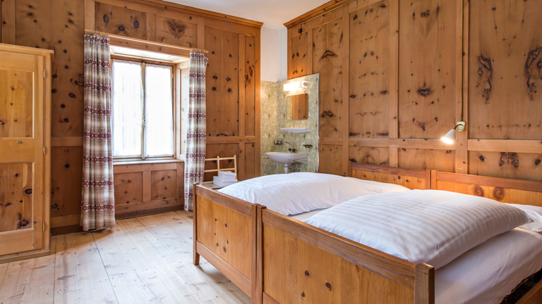Room at Albergo Della Posta.  Classic, spacious timber paneled rooms with private sink. Shower and toilet facilities are shared.  Single room: CHF 950 Double room: CHF 850