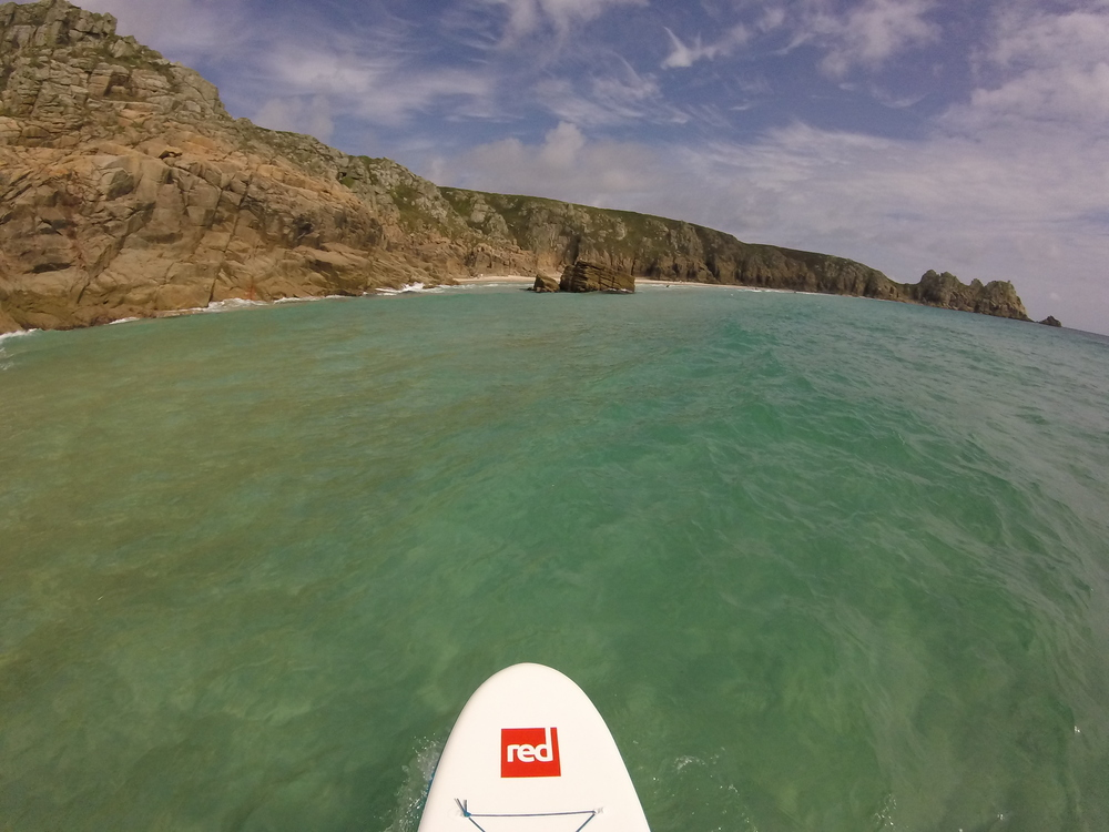 Tropical waters of Porthcurno Stand Up Paddling towards Logan's Rock