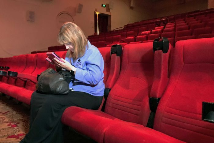 "Cinemagoers are usually urged to switch off mobile phones when the lights dim for a movie, but a new app for the vision-impaired will transform their device and film-going experience. Adelaide woman Sarah Savage said her impairment meant she had never before been to the cinema, and she missed out as well when she and her husband watched TV or movies at home. ""I miss most of the detail, especially if there's lots of darkness,"" she said. The MovieReading app detects the point the film is at, via the phone's microphone, and streams a detailed descriptive audio track, which tells the user what is appearing on the big screen."
