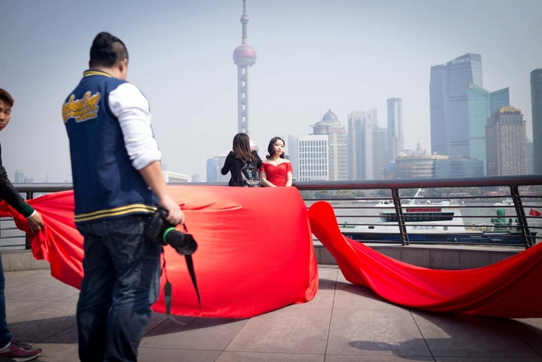 If you've ever travelled to the world's most famous locations and seen Chinese bridal couples posing for over-the-top photo shoots, there's no need to congratulate them yet for their Big Day. Why? Because often the actual wedding could still be another six months away!  What you're witnessing is the cornerstone of China's massive $80 billion wedding industry: the pre-wedding photo shoot. This trend is so huge, couples try to outdo each other with exotic locations and price tags to match. While many couples are happy to pay a few thousand dollars for a set of wedding images, China's jet set have been known to pay up to $500,000 for a series of international, on-location shoots (think an Antarctic backdrop for that kind of price)!
