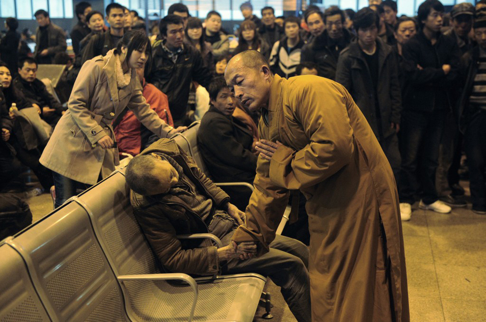 politics-war: A monk prays for an elderly man who had died suddenly while waiting for a train in Shanxi Taiyuan, China.