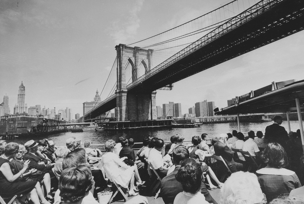 1964: New York City's Brooklyn Bridge is seen looming over a sightseeing boat, July 3, 1964. In the background is the lower Manhattan skyline.