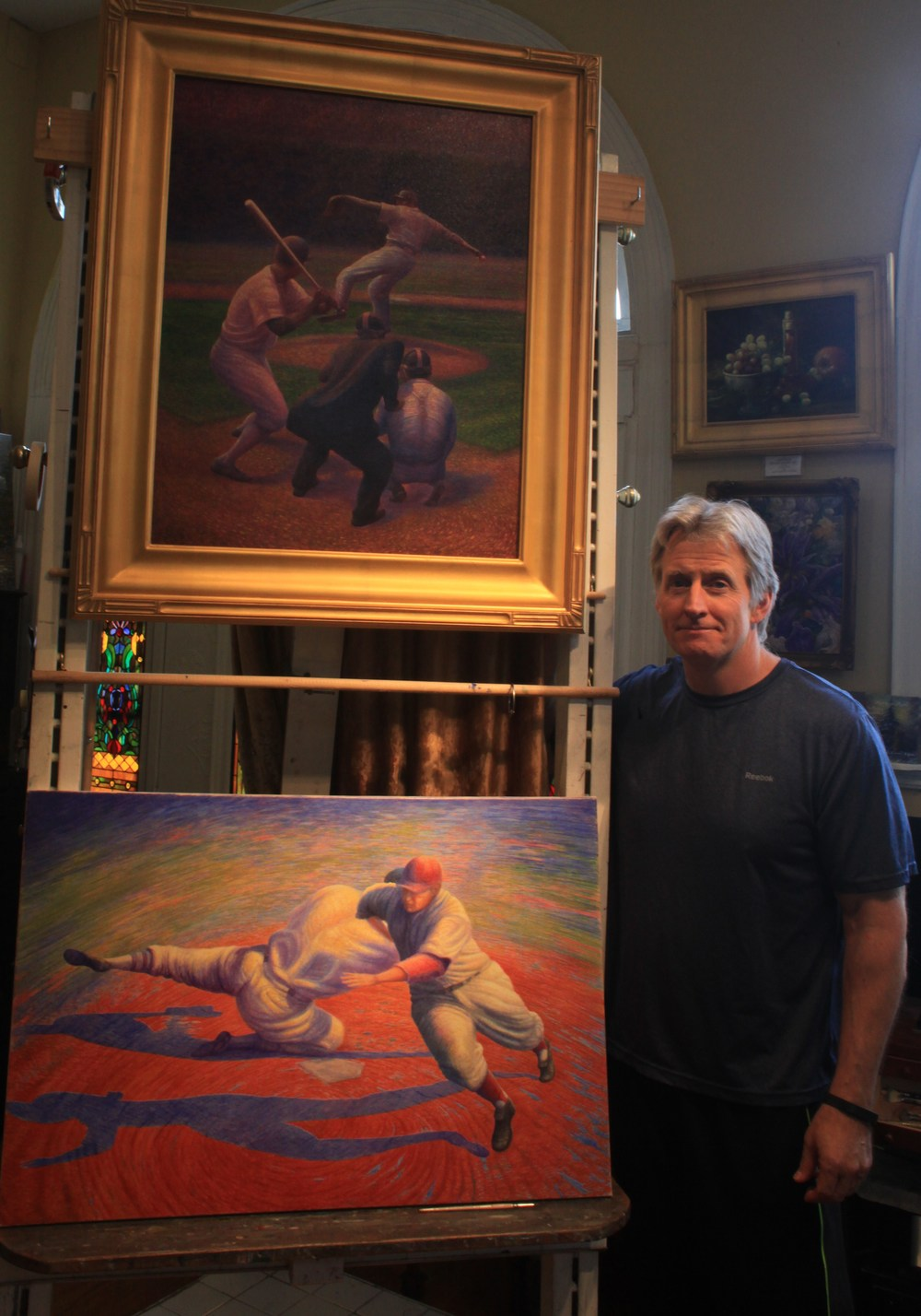 Florence Artist Keith Klein with his two paintings in the exhibit. (Photo by Mike Rutledge)