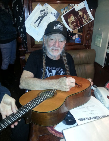 willie_signing_guitar