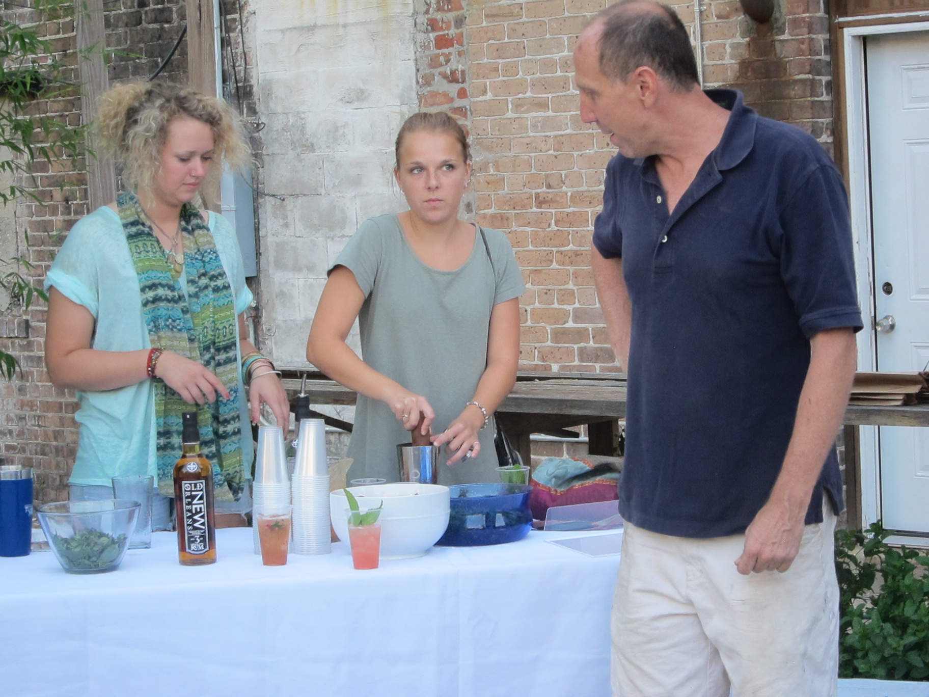 Lee Stafford assists two volunteer bar tenders at the ELC finale party.
