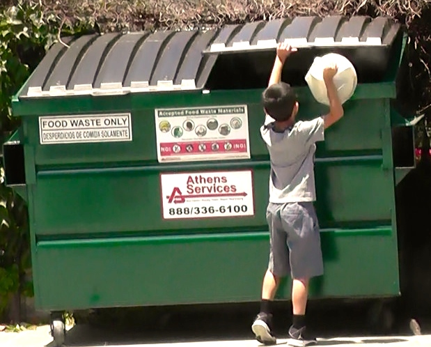 Young resident tosses compostable bag of food waste into new compost dumpster at Lincoln Heights apartment.