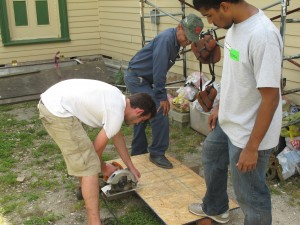 Volunteers Albert and Andrew help Mr. Taylor build an attic hatch cover.