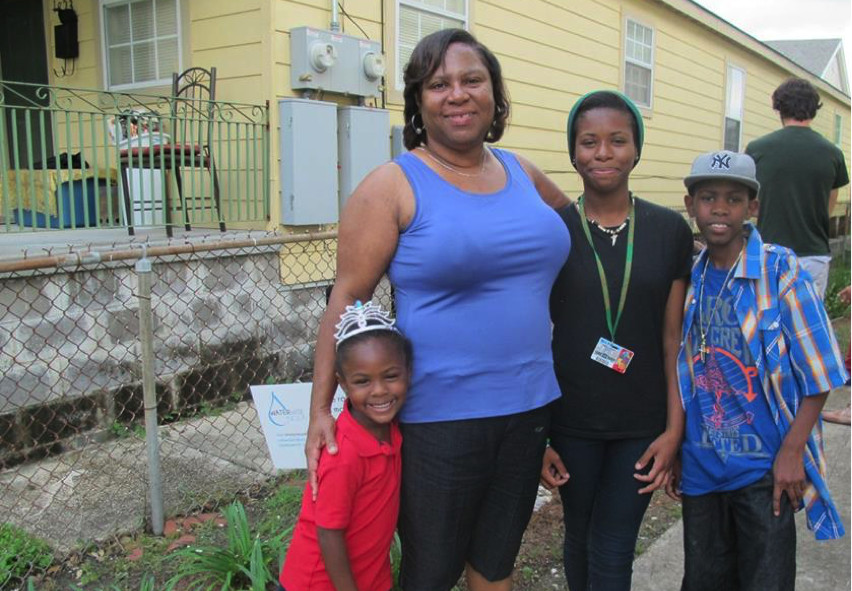 Angela Chalk and her family in front of her raingarden at a celebration party to thank the KIPP Central City Student and Groundworks Green Team for their help on building the garden.