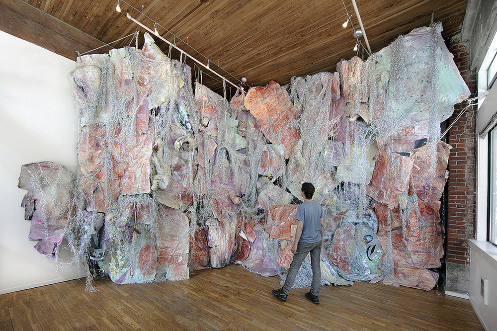 New Person Now , 2014  Yams, Mylar, Paper, Resin, Mirror, Rope, Pigment, Projector, Digital Video Approx. 25 FT wide x 14 FT tall x 6 FT deep  Cascading pastel layers are draped with tinsel and studded with yams in this playful and futuristic rumination of a collapsing sunset.
