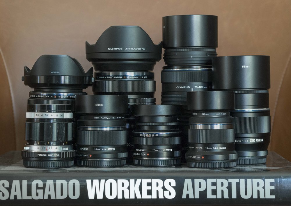 Awh.. the touching family portrait. There is one lens missing (the silver haired step child?), the second, silver 45mm that took the image. Most of the hoods are ebay cheapies. I like metal screw in hoods on top of filters ad throw the caps on a box until it's time to sell the lenses.