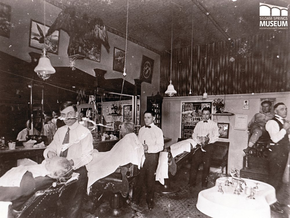 Inside Rapps' Barber Shop around 1920. Rapps' was open in downtown Siloam Springs from 1909 to the mid 1960's. Notice that half of the shop's customers are there for a shave.
