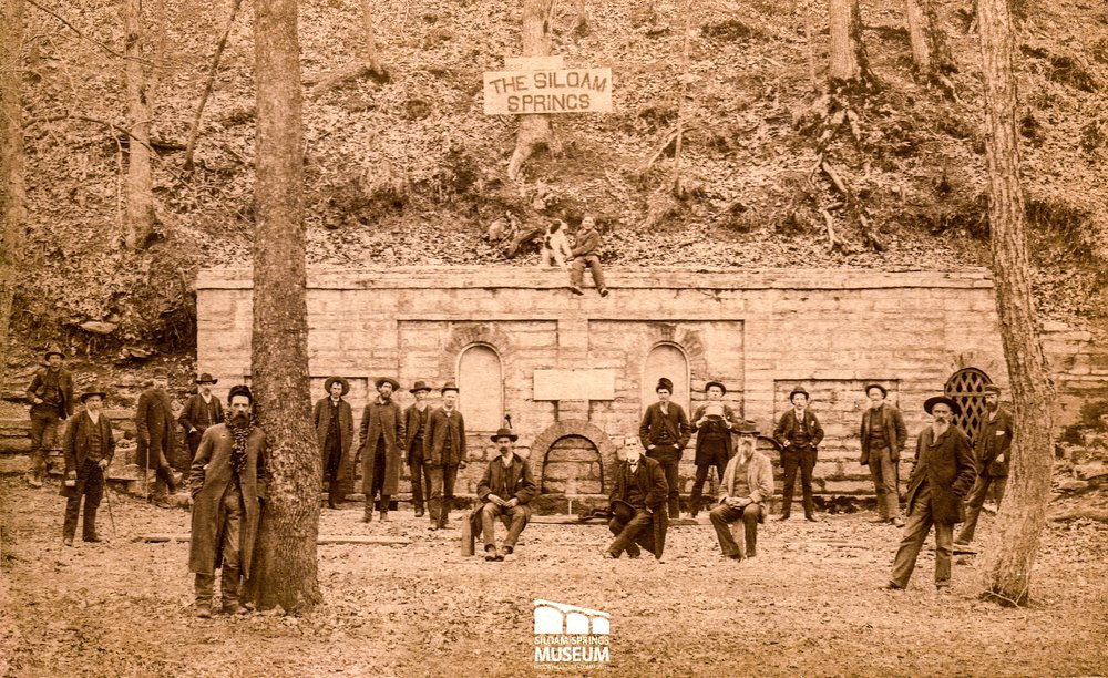 A group of men stand in front of the Siloam Spring around 1885. A boy and his dog sit atop the wall.