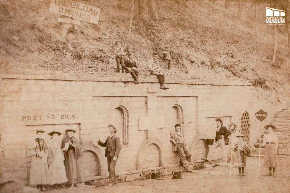 A group of tourists stand near the Siloam Spring around 1895, some of whom may have been from Maine (see the sign held by the girl on the right).