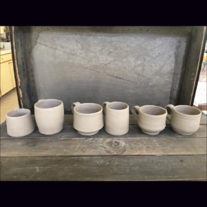 Then handles are made and attached. The mugs are air-dried before going into the kiln for the bisque firing.