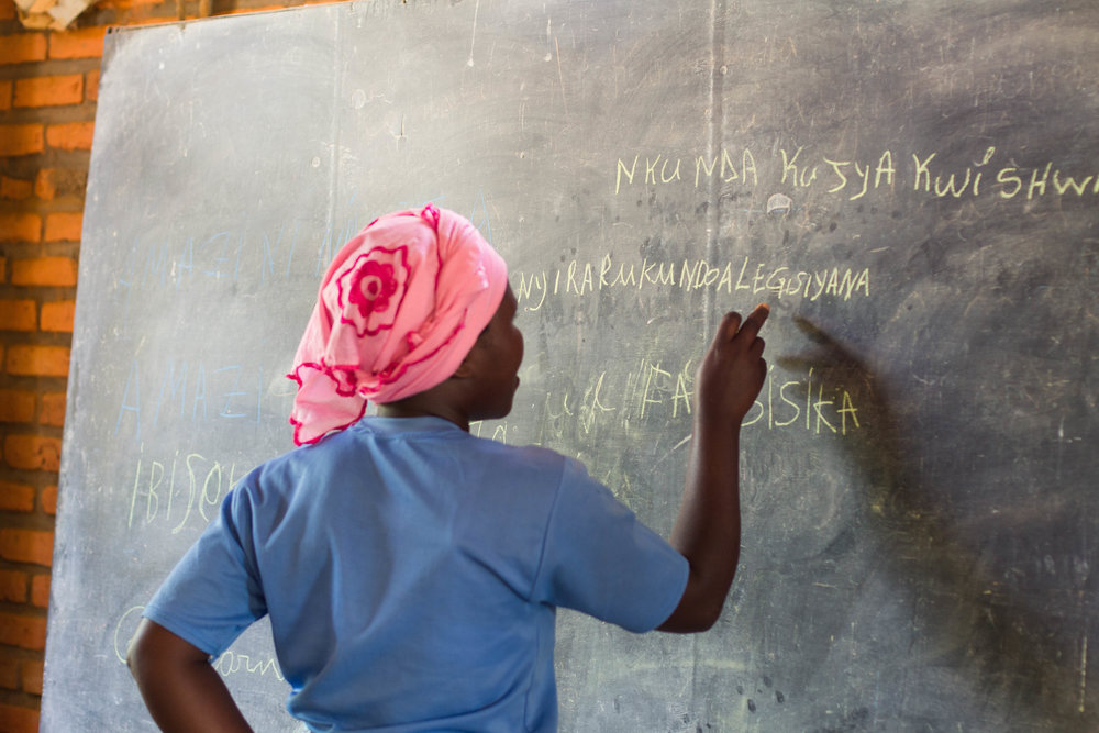 Alegisiyana spells her name on the chalkboard during literacy class.