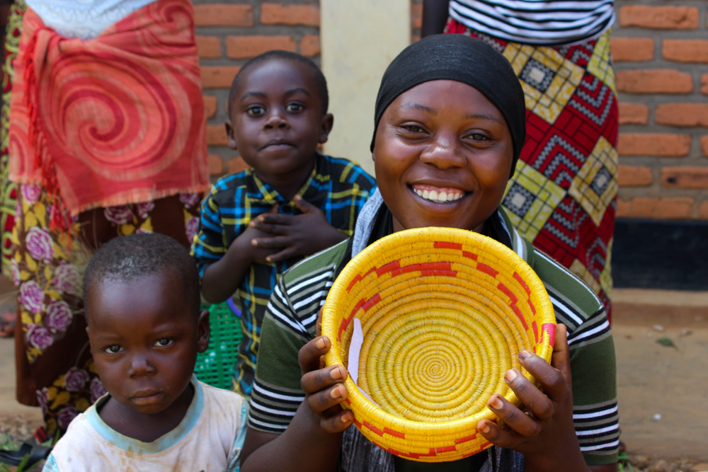 Rwandan artisan poses with her family and beautiful basket she has woven.