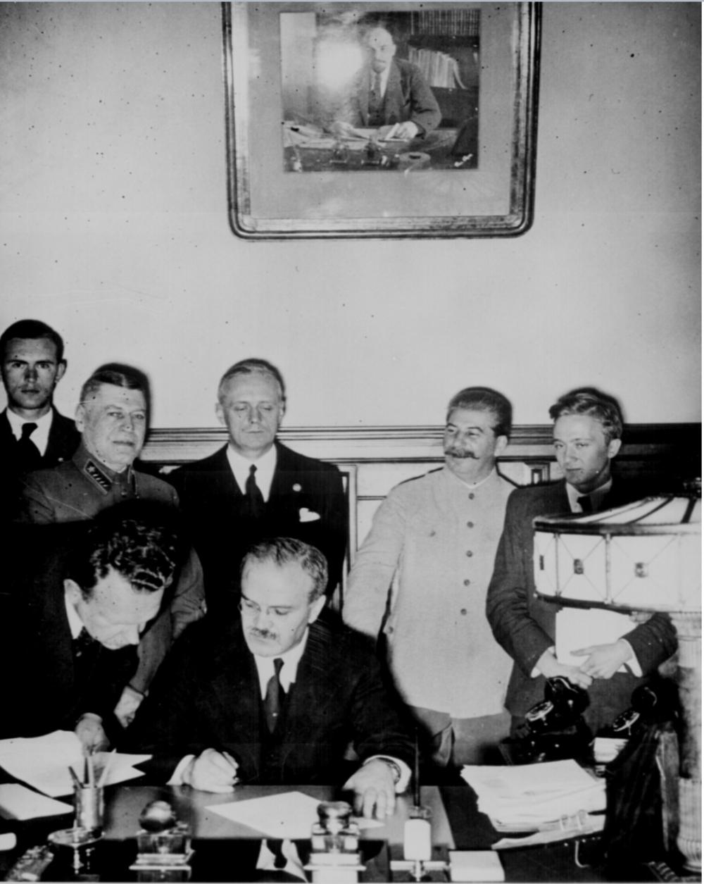 Mólotov (sentado) von Ribbentrop (detrás de Molotov) y Stalin sonriendo (a la izquierda de von Ribbentrop)