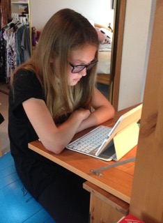 Natasha working on a blog sporting her new glasses