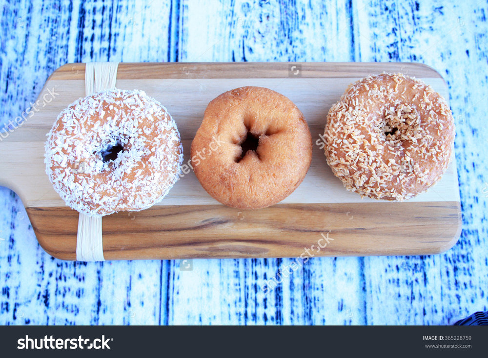 stock-photo-three-donuts-on-a-wooden-cutting-board-on-old-fashion-donuts-one-coconut-one-toasted-almond-in-a-365228759.jpg