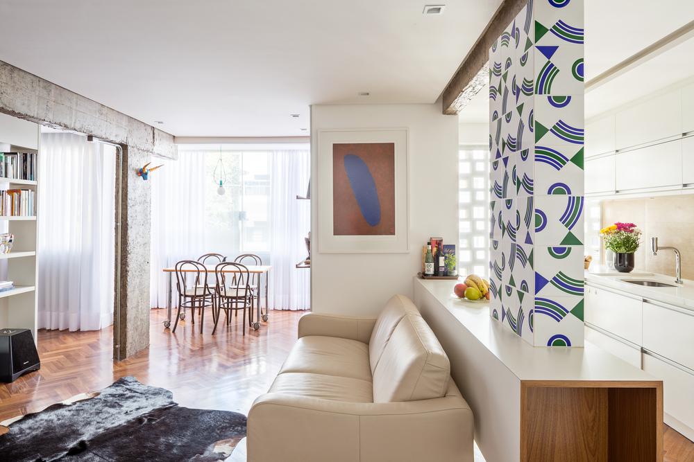 O pilar, revestido com azulejos do Athos Bulcão, sustenta a balcão em marcenaria, que separa sutilmente os ambientes.