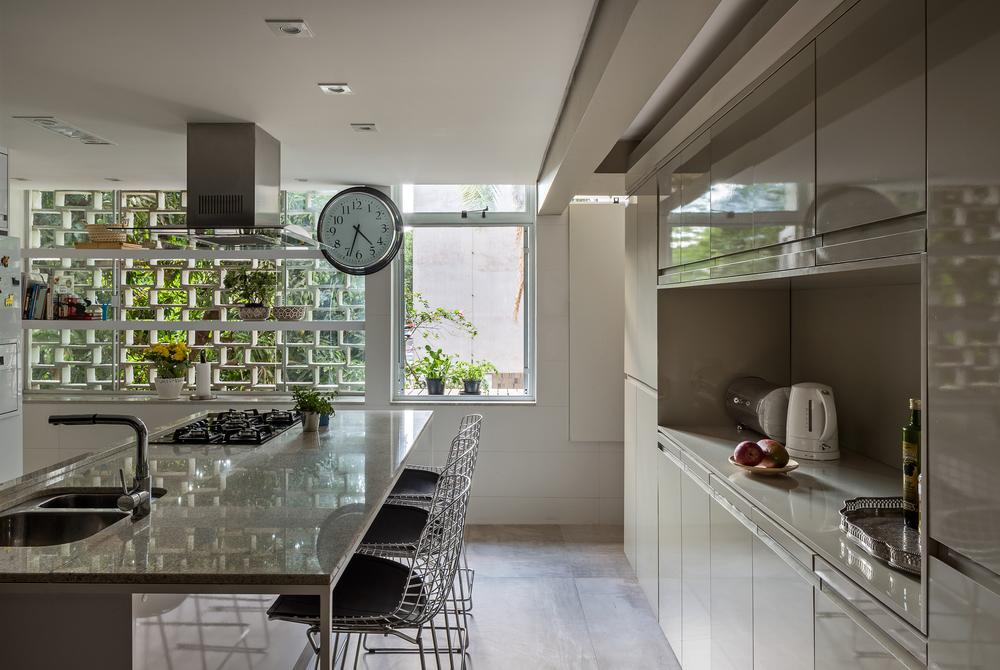 O cobogó, antes pertencente somente à área de serviço, agora traz luz à nova cozinha.