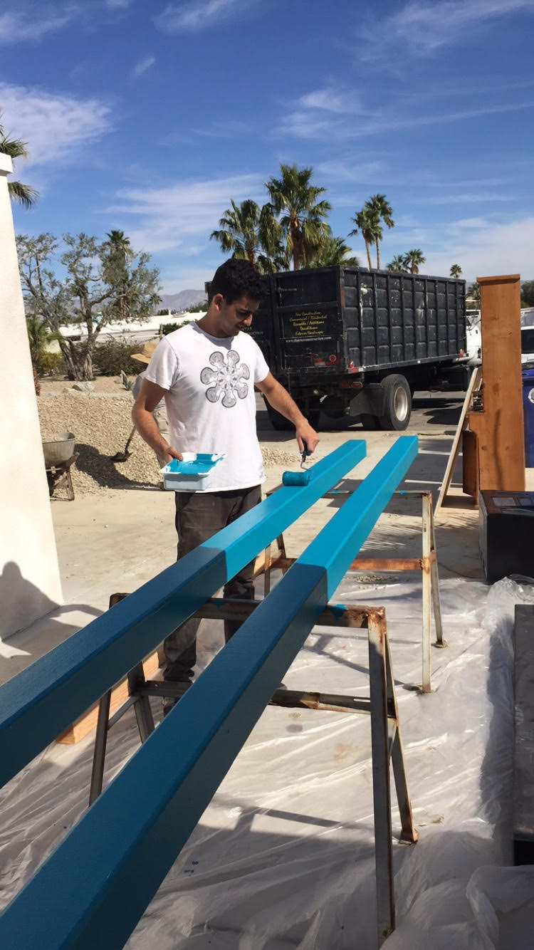 Shawn, getting his hands dirty by hand painting metal posts that will be used to create a terrace.