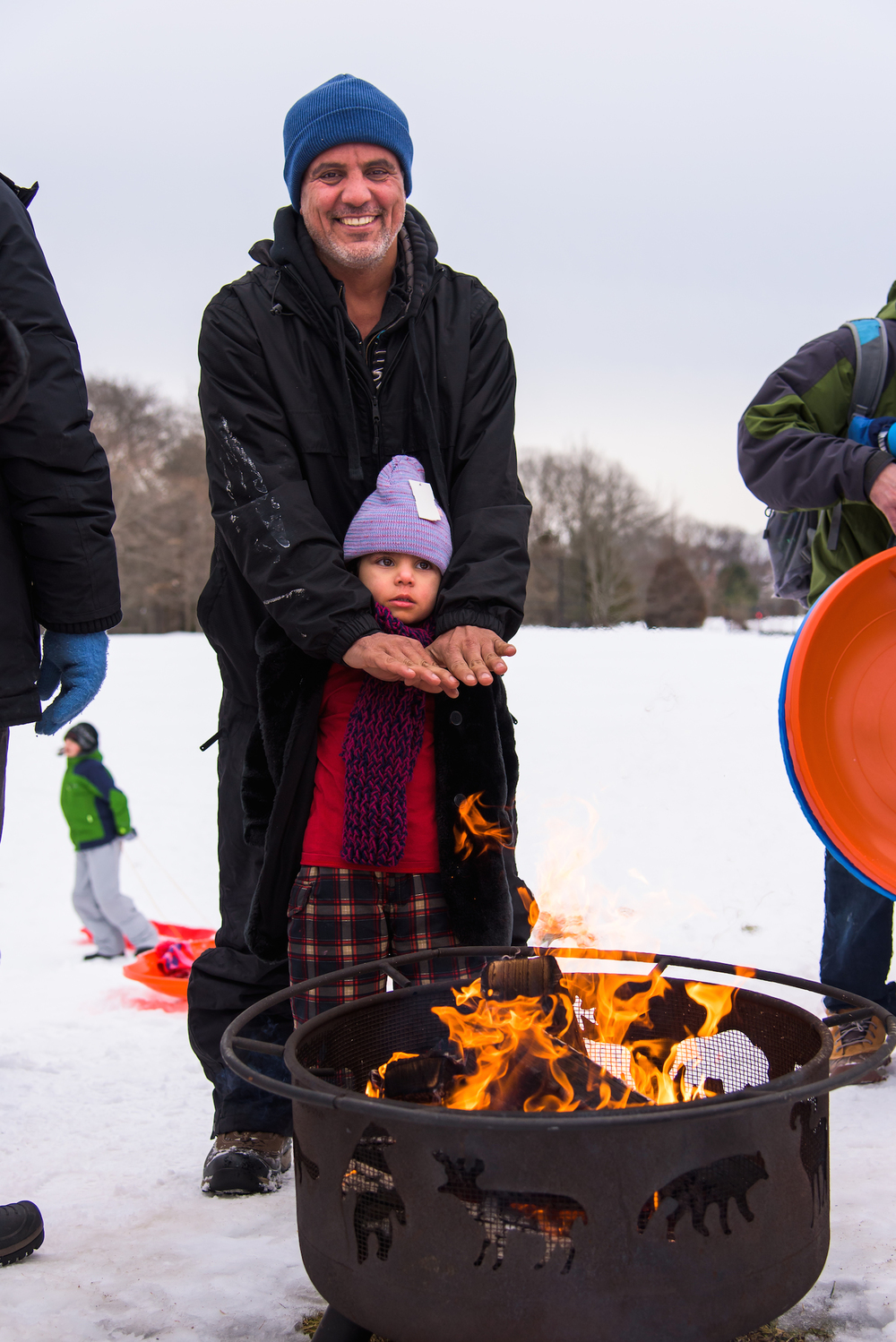 Nour Almamouri, 3, and Ahmad Almamouri, 42, of Portland by way of Iraq warm themselves by the fire.