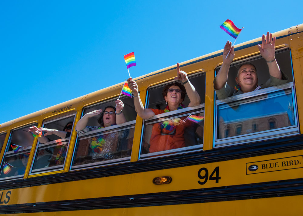 Representatives of Portland Public Schools wave to the crowd on Congress Street from their big yellow school bus at the Portland Pride Parade on June 18, 2016.