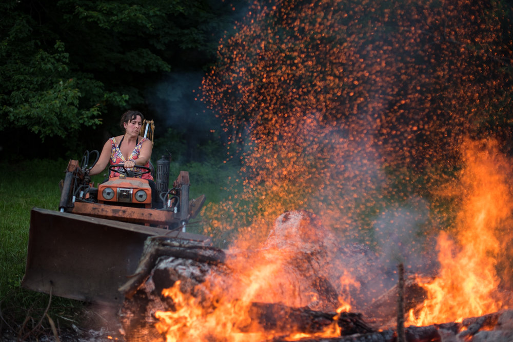 Mary Rafter tends to a bonfire in preparation for a backyard lobster bake in Bremen Sunday, July 3, 2016.