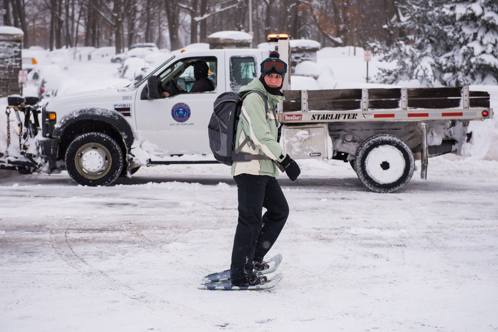 7:51am – Ashley Lazarz, a dietician at Maine Medical Center, snowshoes to work along Deering Ave. In the background, Dave Blackwell plows the entrance to Deering Oaks Park.