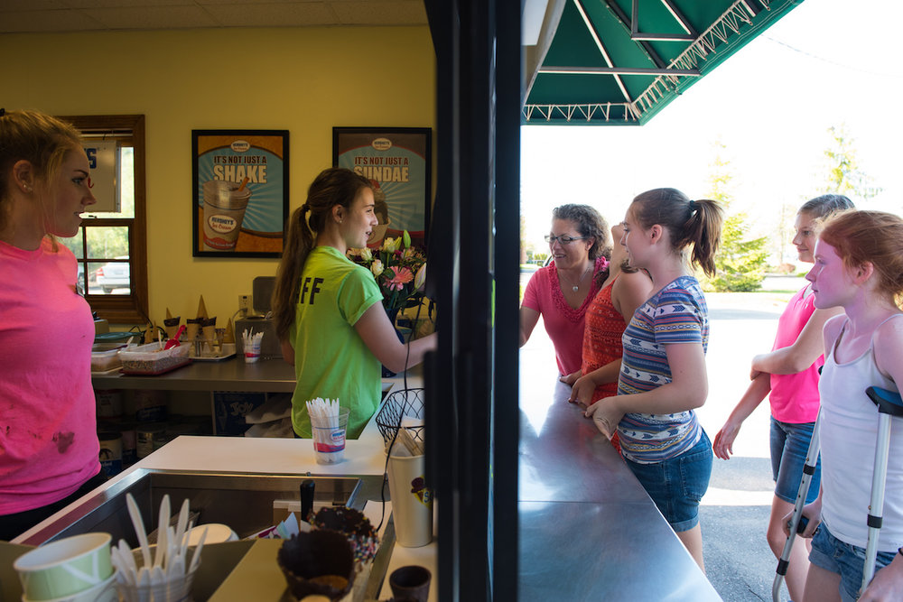 Bri Douglas hands an ice cream cone to Jen Libby of Falmouth at Scoops Ice Cream in Falmouth Friday, May 19, 2017.